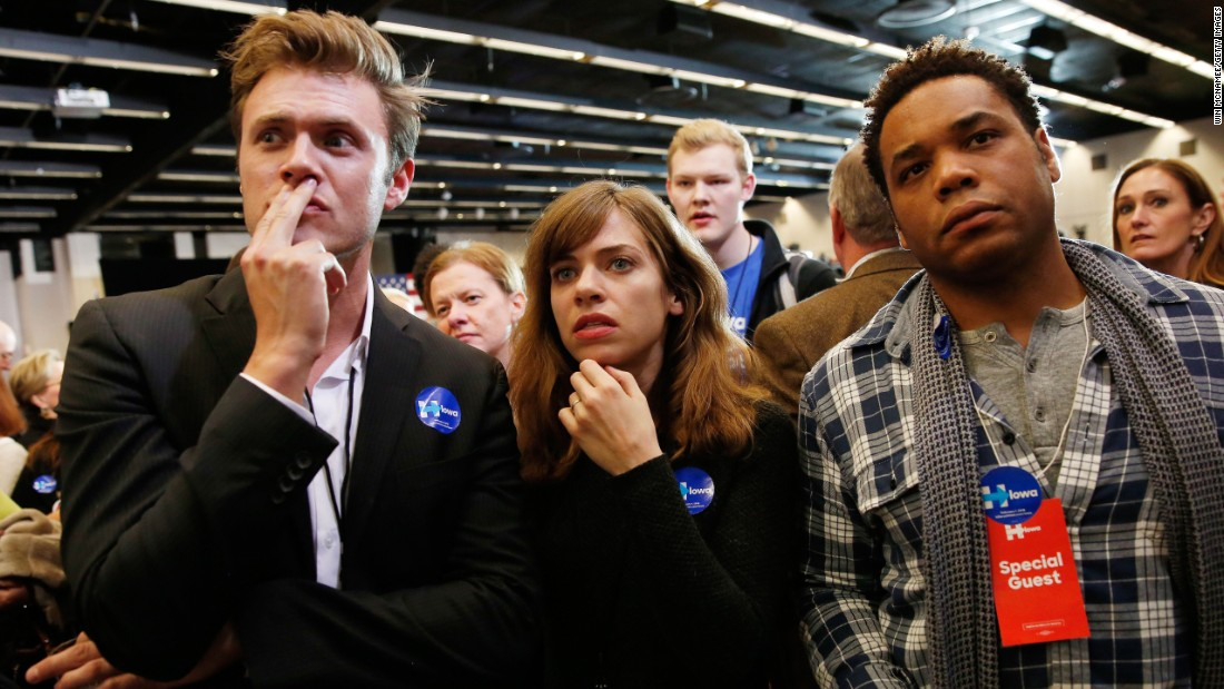 Clinton supporters in Des Moines watch the television as caucus results roll in.