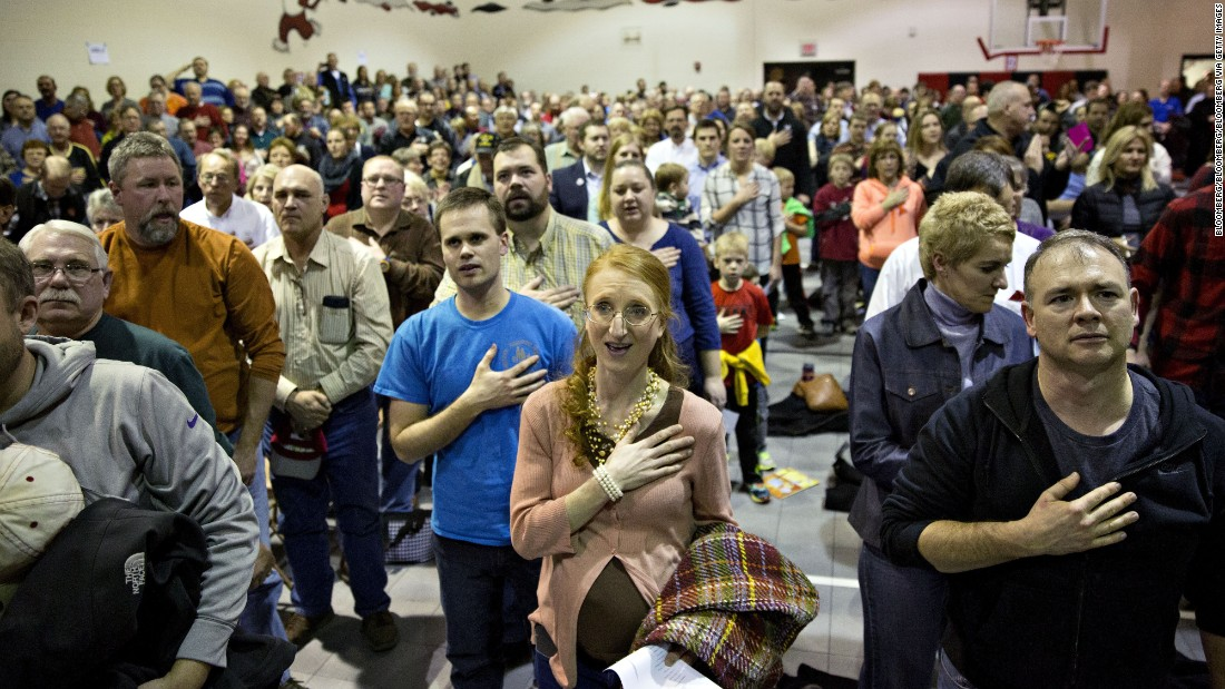 Republican voters sing the national anthem in the gymnasium of an elementary school in Adel, Iowa.