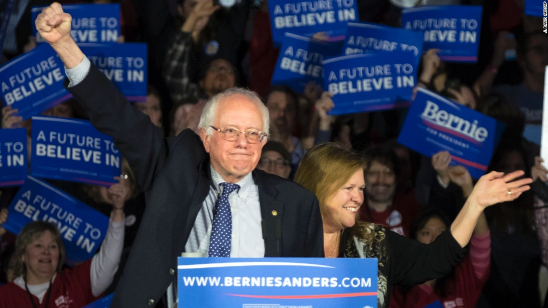 "Sanders and his wife, Jane, acknowledge the crowd as he arrives for his caucus night rally in Des Moines. ""Nine months ago, we came to this beautiful state, we had no political organization, we had no money, we had no name recognition and we were taking on the most powerful political organization in the United States of America,"" Sanders said. ""And tonight, while the results are still not known, it looks like we are in a virtual tie."""