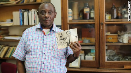 "Entomologist Louis Mukwaya holds a picture of Alexander Haddow, the scientist who first identified Zika virus in 1947. ""He was a very hardworking man,"" Mukwaya said of Haddow. Mukwaya has been working at the institute since 1965."