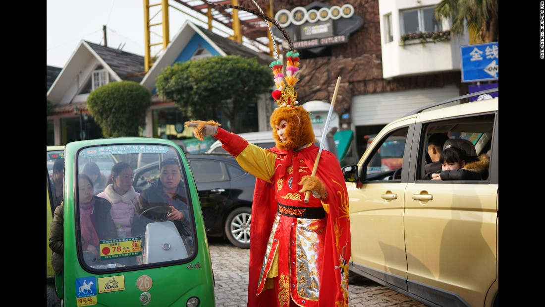 Security personnel dressed as the Monkey King gives directions to tourists in Chongqing, China, on February 2.