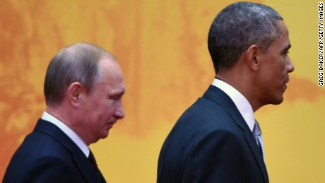 U.S. President Barack Obama walks to a group photo session with Russian President Vladimir Putin (L) at the Asia-Pacific Economic Cooperation (APEC) summit at Yanqi Lake, north of Beijing on November 11, 2014.