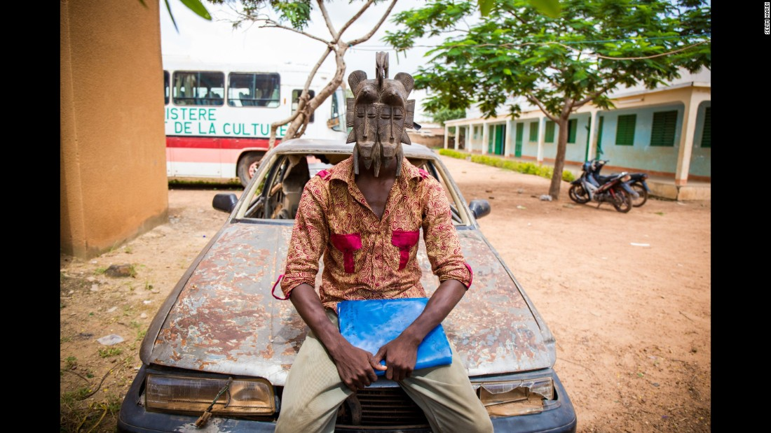 Jakou, 24, is a cartoonist and yoga teacher who moved to Burkina Faso after fleeing the Ivorian conflict in 2010. He is wearing a mask of peace from the Senufo people.