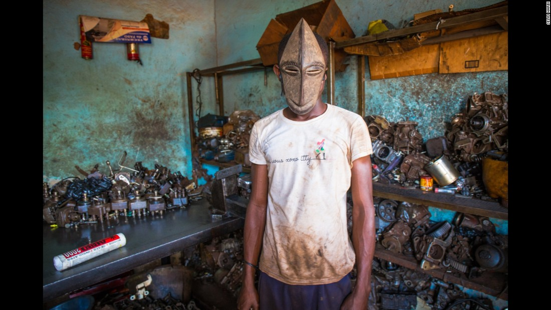 "Hoseni, 17, repairs broken cars in Abidjan, Ivory Coast. He is called ""Petit,"" or small, and his monkey mask is from the Hembe ethnic group."
