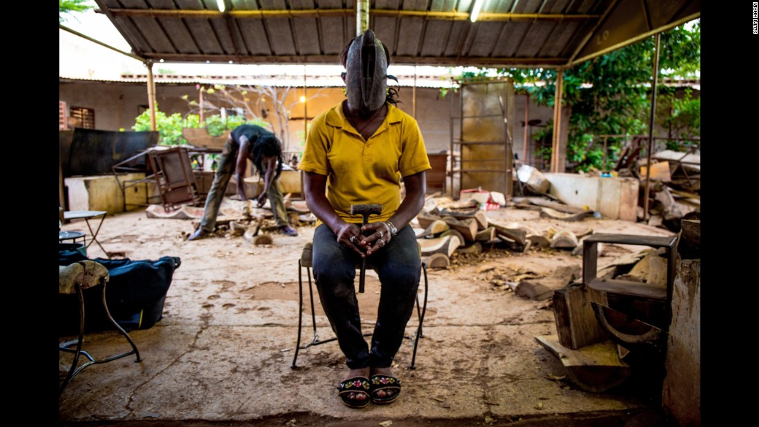 Susanne, 23, wears a mask from the Dogon people. She is training to be a sculptor in Ouagadougou.