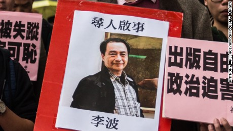 """In this picture taken on January 3, 2016, a protestor holds up a missing person notice for Lee Bo, 65, the latest of five Hong Kong booksellers from the same Mighty Current publishing house to go missing, as they walk towards China's Liaison Office in Hong Kong. Britain confirmed on January 5 that one of five missing Hong Kong booksellers feared detained by Chinese authorities is a UK citizen, saying it was """"deeply concerned"""" over the disappearances. AFP PHOTO / ANTHONY WALLACE / AFP / ANTHONY WALLACE        (Photo credit should read ANTHONY WALLACE/AFP/Getty Images)"""