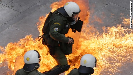 Riot policemen try to avoid a petrol bomb thrown by protesters during a 24-hour nationwide general strike in Athens, Thursday, Feb. 4, 2016. Clashes have broken out between Greek police and youths throwing fire bombs and stones, as tens of thousands of people march through central Athens to protest planned pension reforms.(AP Photo/Thanassis Stavrakis)