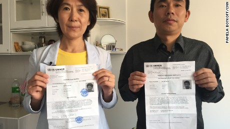 Chinese dissidents Yu Yanhua, left, and Yan Bojun pose with their U.N. asylum  seeker documents from the UNHCR in Bangkok. They fled China together for safety in Thailand but now fear their government will come after them even outside of its borders.