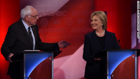 Graphic content / US Democratic presidential candidates Hillary Clinton (R) and Bernie Sanders chat during a break as they participate in the MSNBC Democratic Candidates Debate at the University of New Hampshire in Durham on February 4, 2016.