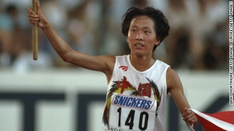 1993:  Junxia Wang of China carries two Chinese flags on a lap of honour after winning the 10 000 metres event at the World Championships in Stuttgart, Germany. \ Mandatory Credit: Gray  Mortimore/Allsport