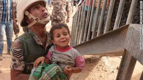 A Jordanian soldier carries a young Syrian refugee at the al-Roqban makeshift camp, on the border with Syria, before driving a group of refugees to the eastern town of Ruwaished where they will be welcomed and checked by the Jordanian authorities on September 10, 2015. The latest batch of refugees from neighbouring Syria will be sent from Ruwaished, around 380 km from the capital Amman, to various refugee camps and temporary settlements across the country. AFP PHOTO / KHALIL MAZRAAWI        (Photo credit should read KHALIL MAZRAAWI/AFP/Getty Images)