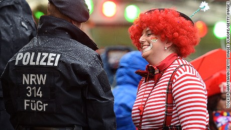 A woman in fancy dress speaks to the police as she takes part in Cologne's annual Carnival celebration.
