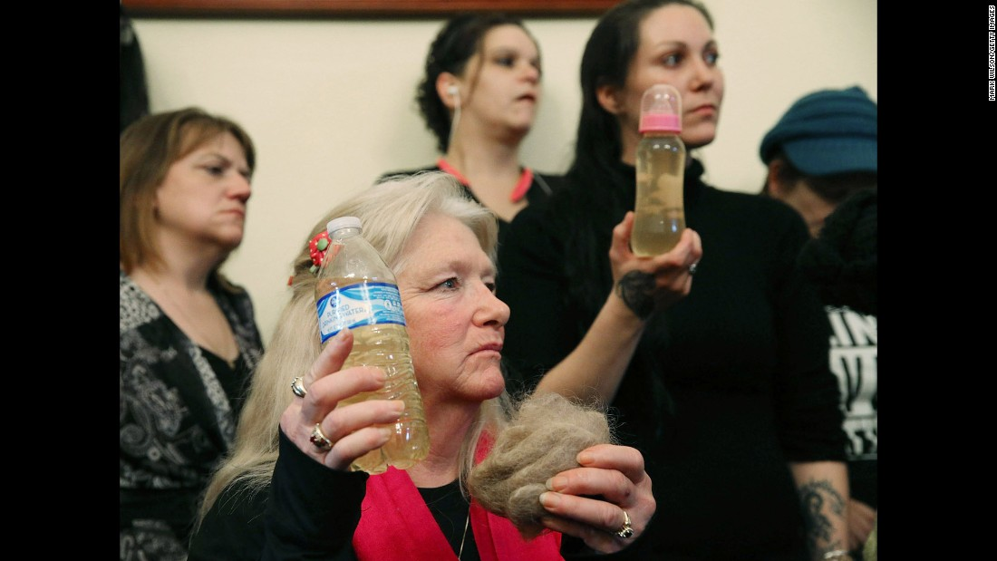 """Flint, Michigan, residents Gladyes Williamson, center, and Jessica Owens, right, attend the House Committee on Oversight and Government Reform hearing on Capitol Hill about the Flint <a href=""""http://www.cnn.com/2016/02/03/us/flint-michigan-water-crisis/"""" target=""""_blank"""">water crisis</a>. Williamson and Owens hold bottles of contaminated water, and Williamson shows a clump of her hair. The two traveled to Washington by bus with other families to demand that Gov. Rick Snyder be brought to testify before Congress. The House hearing was on Wednesday, February 3."""