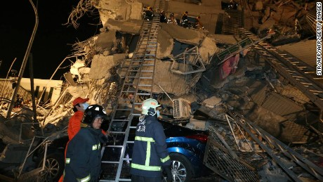 Rescue personnel search through debris at the site of a collapsed building in the southern Taiwanese city of Tainan following a strong 6.4-magnitude earthquake that struck the island early on February 6, 2016.  Rescuers were battling to free more than 100 people trapped in a collapsed building in the southern Taiwanese city of Tainan following a strong 6.4-magnitude earthquake that struck the island.   AFP PHOTO / TAIWAN OUT / AFP / STR        (Photo credit should read STR/AFP/Getty Images)