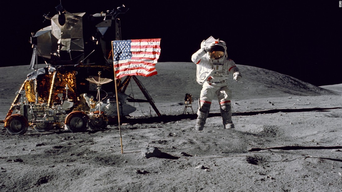 Young leaps from the surface of the moon as he salutes the U.S. flag.