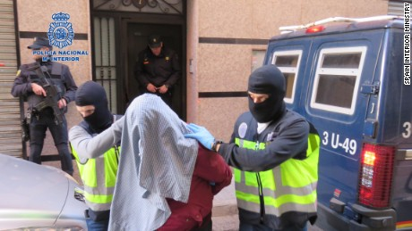 Spanish police wearing balaclavas escort one of the terror suspects arrested Sunday