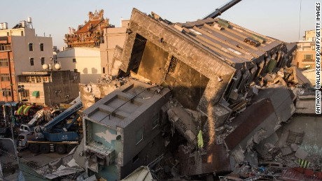 This general view shows cranes and heavy equipment being used for rescue operations at the site where a building which collapsed in the 6.4 magnitude earthquake, in the southern Taiwanese city of Tainan on February 8, 2016.