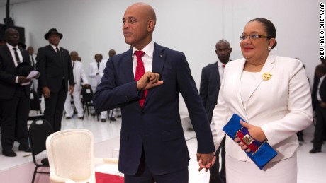 Haiti's President Michel Martelly stands with his wife Sophia before they leave Parliament chambers, in Port-au-Prince, Haiti, Sunday, Feb. 7, 2016.  Martelly made his farewell address to Parliament Sunday, leaving office with no leader yet chosen to fill the void left by his departure. Lawmakers are beginning a process to patch together a short-term interim government. (AP Photo/Dieu Nalio Chery)