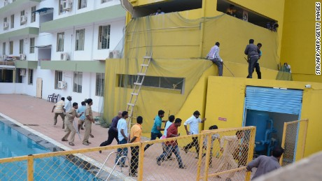 Panicked men run for safety as the leopard roams loose by the school pool Sunday in Bangalore.