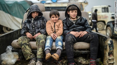TOPSHOT - Children sit on a car as Syrians fleeing the northern embattled city of Aleppo wait on February 6, 2016 in Bab al-Salama, near the city of Azaz, northern Syria, near the Turkish border crossing. Thousands of Syrians were braving cold and rain at the Turkish border Saturday after fleeing a Russian-backed regime offensive on Aleppo that threatens a fresh humanitarian disaster in the country's second city. Around 40,000 civilians have fled their homes over the regime offensive, according to the Syrian Observatory for Human Rights monitor. / AFP / BULENT KILIC        (Photo credit should read BULENT KILIC/AFP/Getty Images)