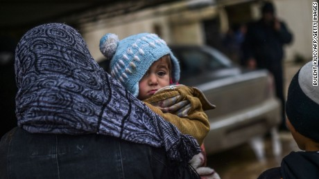 Refugees wait near the Turkish border crossing gate as Syrians fleeing the northern embattled city of Aleppo wait on February 6, 2016.