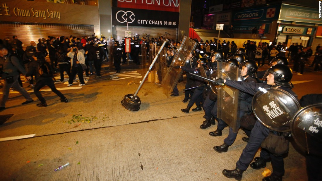 Riot police move forward to the protesters on a street in Hong Kong's Mong Kok district, Tuesday, February 9, 2016.