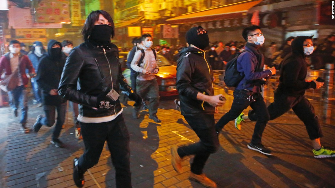 Rioters carry bricks along a street in Mong Kok in the early morning of February 9.