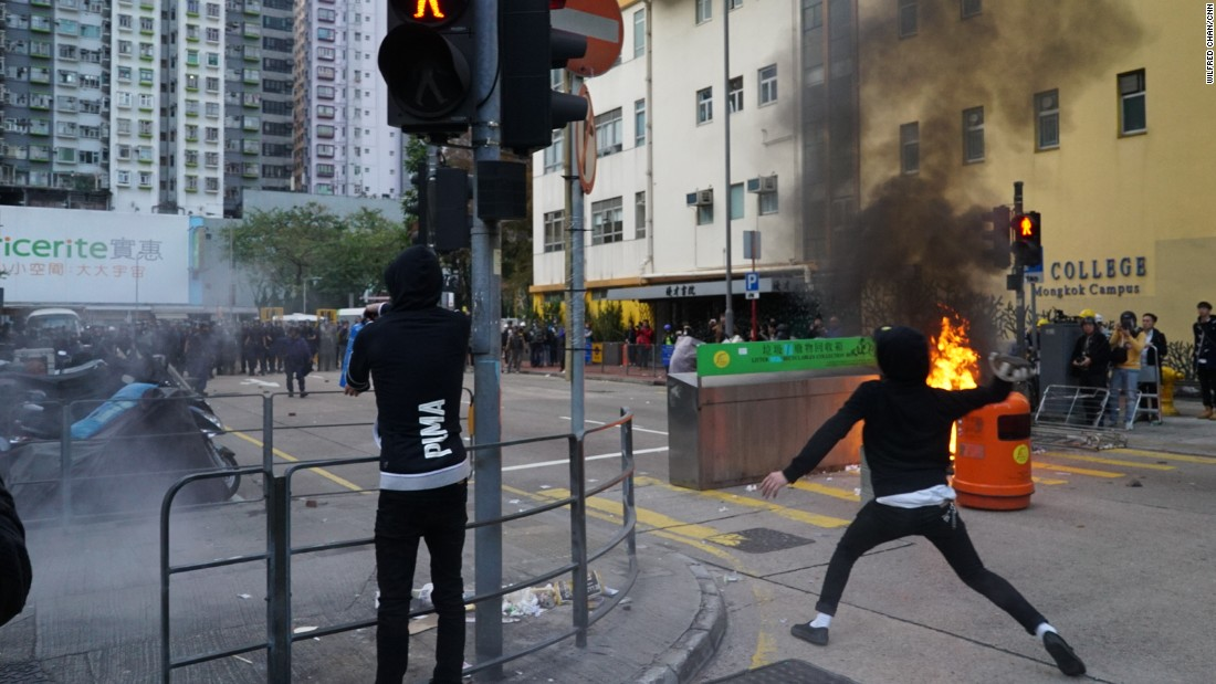 A protester hurls a brick at riot police during clashes in Mong Kok early February 9.