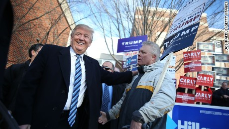 Republican presidential candidate Donald Trump greets people as he visits a polling station as voters cast their primary day ballots on February 9, 2016 in Manchester, New Hampshire.
