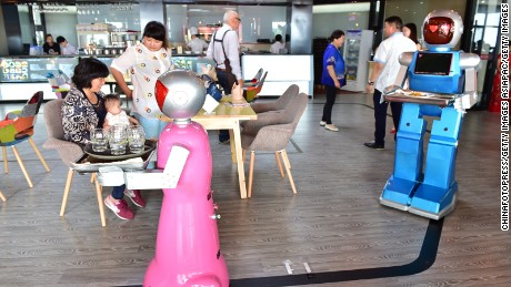 "YIWU, CHINA - MAY 18:  (CHINA OUT) A couple of robot waiters deliver meals for customers at robot-themed restaurant on May 18, 2015 in Yiwu, Zhejiang province of China. Sophomore Xu Jinjin in 22 years old from Hospitality Management of Yiwu Industrial and Commercial College managed a restaurant where a pair of robot acted as waiters. The ""male"" one was named ""Little Blue"" (for in blue color) and the ""female"" one was ""Little Peach"" (for in pink) and they could help order meals and then delivered them to customers along the magnetic track and said: ""Here're your meals, please enjoy"". According to Xu Jinjin, They had contacted with the designer to present more robot waiters to make the restaurant a real one that depends completely on robots.  (Photo by ChinaFotoPress via Getty Images)"