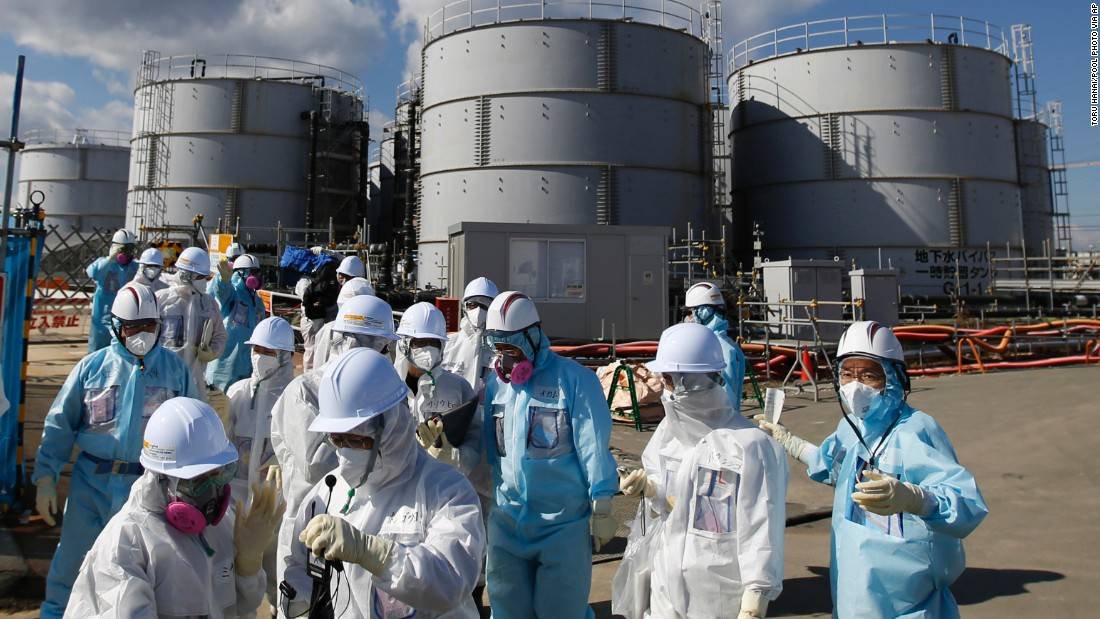 TEPCO employees, in blue protective suits, brief a press group in front of storage tanks for radioactive water on Februray 10.
