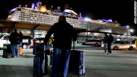 A passenger from the Royal Caribbean cruise ship, Anthem of the Seas, awaits transportation after arriving at Cape Liberty cruise port, Wednesday, Feb. 10, 2016, in Bayonne, N.J. Carrying 4,500 passengers and 1,600 crew members, the ship returned early from a seven-day cruise to the Bahamas after it was battered by a major storm in the Atlantic Ocean. (AP Photo/Julie Jacobson)