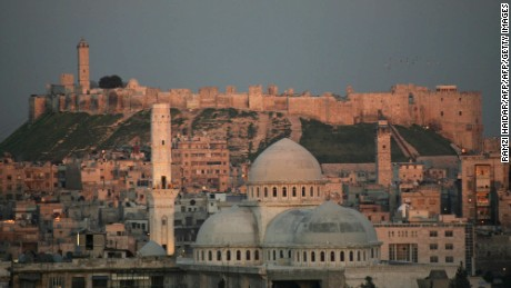 """A picture taken 17 March 2006 shows a general view of the historic Syrian city of Aleppo, 350 kms north of Damascus, with its landmark cytadel in the background. Hundreds of Arab and foreign personalities will gather in Aleppo this weekend to celebrate its choice as the Arab world's capital of Islamic culture for 2006. Syrian Culture Minister Riad Nassan Agha said yesterday Aleppo was chosen by the Organization of the Islamic Conference (OIC) because of its role as the """"main point of passage between East and West."""" Two days of inaugural festivities will kick off 18 March 2006 with the rededication of the 12th-century Great Mosque (C), which has been under restoration for the past five years. AFP PHOTO/RAMZI HAUDAR (Photo credit should read RAMZI HAIDAR/AFP/Getty Images)"""