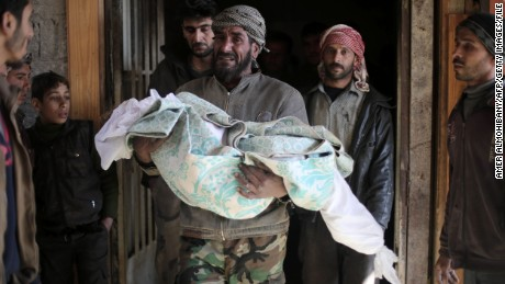 TOPSHOT - EDITORS NOTE: Graphic content / The father of Maram, a ten-year-old Syrian girl who was reportedly killed in airstrikes that hit a kindergarten, carries her body before her funeral in the village of Deir al-Asafir in the rebel-held region of Eastern Ghouta, on the outskirts of the Syrian capital Damascus on January 12, 2016.   / AFP / AMER ALMOHIBANY        (Photo credit should read AMER ALMOHIBANY/AFP/Getty Images)
