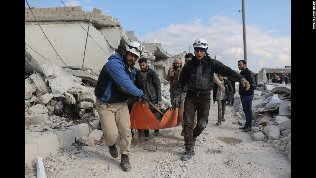 "Members of the ""White Helmets"" civil defense volunteers carry the body of a man killed in a Russian airstrike in Andan town in the countryside north of of Aleppo."