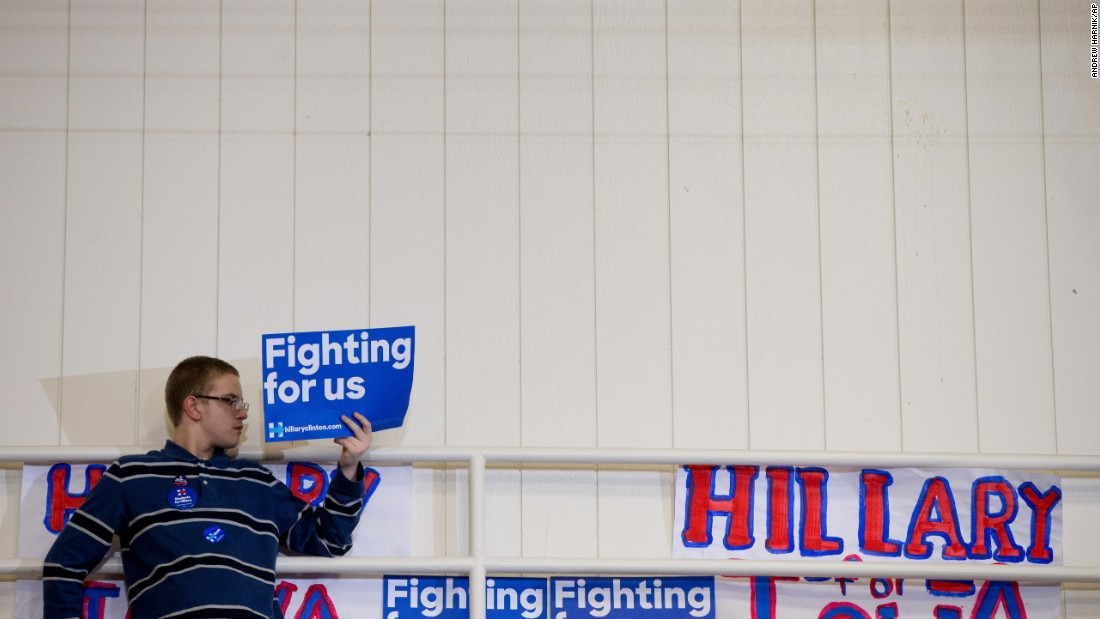 """Hillary Clinton has used the slogan, """"Hillary for America"""" and also had supporters display posters saying """"Fighting for us."""" A member of the audience holds a campaign sign at the top of a set of bleachers as Clinton speaks in Iowa on January 30."""