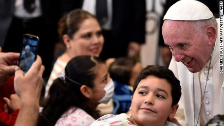 """Pope Francis is photographed with a little patient during his visit to the Federico Gómez children's hospital in Mexico on February 14, 2016.Pope Francis celebrated an open-air mass with 300,000 Catholic faithful in a crime-plagued Mexican city on Sunday, urging them to create a country free of emigration and """"merchants of death.""""   AFP PHOTO / GABRIEL BOUYS / AFP / GABRIEL BOUYS        (Photo credit should read GABRIEL BOUYS/AFP/Getty Images)"""