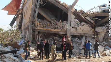 People gather around the rubble of a hospital supported by Doctors Without Borders (MSF) near Maaret al-Numan, in Syria's northern province of Idlib, on February 15, 2016, after the building was hit by suspected Russian air strikes.