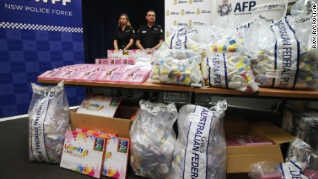 Officers stand by a display of confiscated drugs in Sydney, Monday, Jan. 15, 2016. Australian Federal Police said they had seized 720 liters (190 gallons) of the illicit drug methylamphetamine worth more than 1 billion Australian dollars ($700 million). (AP Photo/Rick Rycroft)