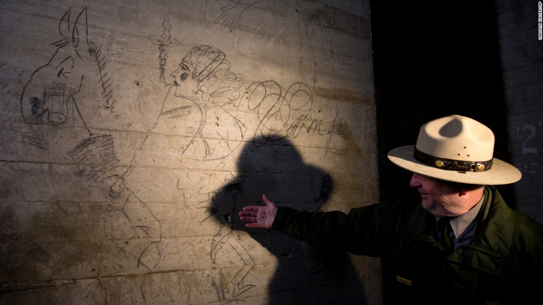 Sean Kennealy of the National Park Service points out drawings on a concrete pillar Monday, February 15. The renovation will include providing visitors with a look at graffiti left by construction workers building the monument.