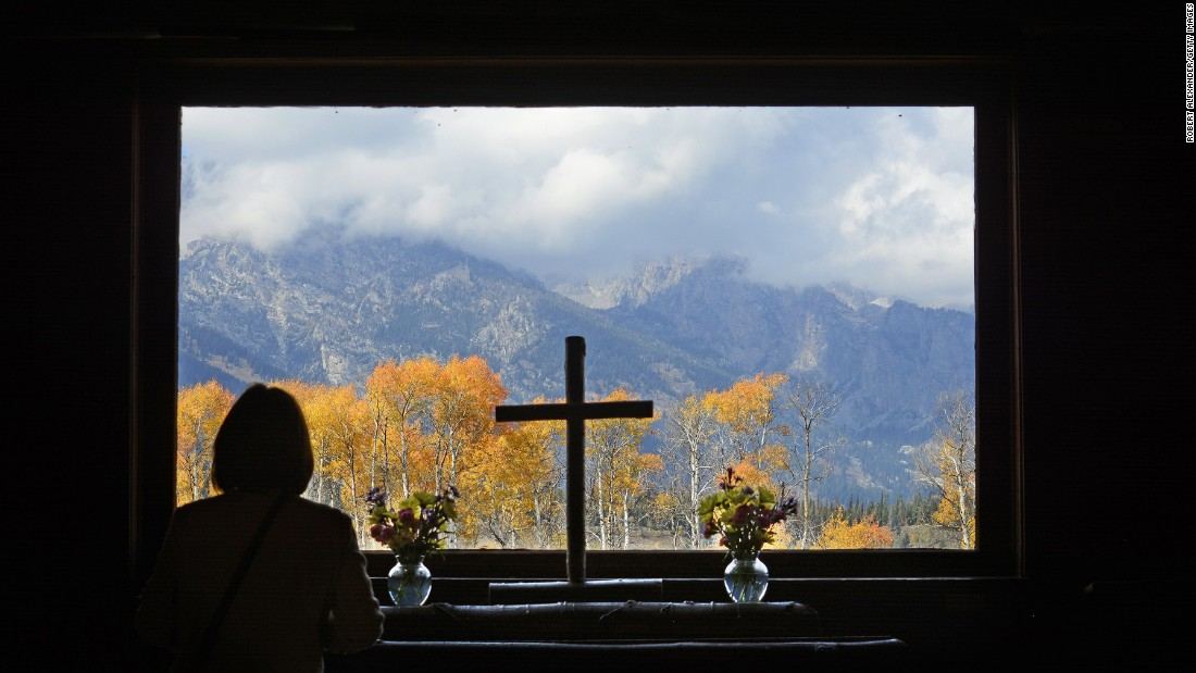 "A park visitor takes in the autumn view from the alter window at the Chapel of Transfiguration in <a href=""http://www.cnn.com/2013/05/30/travel/national-parks-grand-teton/"">Grand Teton National Park</a> in Wyoming. A nearby Episcopal church built the chapel in 1925 to serve nearby guests and dude ranch workers, before the area became a national park."