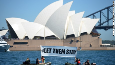 "Members of the environmental group Greenpeace hold up a sign that reads ""#LET THEM STAY"" in front of the Opera House in Sydney on February 14, 2016.  An Australian hospital in Brisbane has refused to send an asylum-seeker baby back to detention in Nauru as momentum builds across the country against offshore Pacific camps for used by the Australia government for processing refugees who try to get to Australia. AFP PHOTO / Peter PARKS / AFP / PETER PARKS        (Photo credit should read PETER PARKS/AFP/Getty Images)"