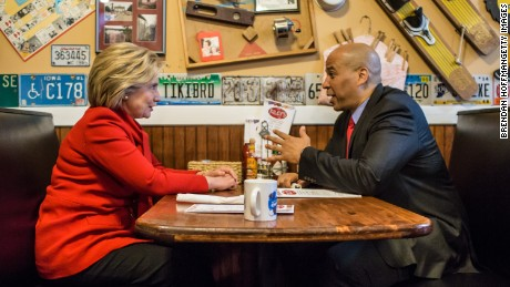 Democratic presidential candidate Hillary Clinton (L) talks with Sen. Cory Booker (D-NJ) at Riley's Cafe on January 24, 2016 in Cedar Rapids, Iowa.