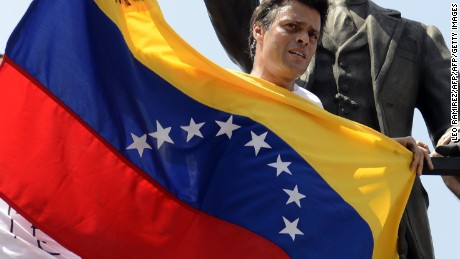 Leopoldo Lopez, an ardent opponent of Venezuela's socialist government facing an arrest warrant after President Nicolas Maduro ordered his arrest on charges of homicide and inciting violence, stands at the monument of Cuba's most important independence-era hero, Jose Marti, as he demonstrates with a national flag in Caracas before turning himself in to authorities, on February 18, 2014. Fugitive Venezuelan opposition leader Lopez, blamed by Maduro for violent clashes that left three people dead last week, appeared at an anti-government rally in eastern Caracas and quickly surrendered to the National Guard after delivering a brief speech. AFP PHOTO / LEO RAMIREZ        (Photo credit should read LEO RAMIREZ/AFP/Getty Images)