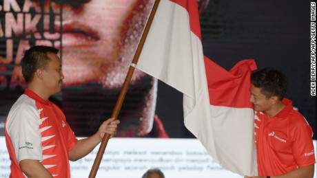 Indonesian Rio Haryanto (R) kisses the national flag next to Sport and Youth Minister Imam Nachrowi (L) during a press conference in Jakarta on February 18, 2016.  Haryanto, the first Indonesian driver in Formula One, will join British Formula One team Manor in 2016.  AFP PHOTO / ADEK BERRY / AFP / ADEK BERRY        (Photo credit should read ADEK BERRY/AFP/Getty Images)