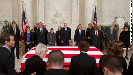 WASHINGTON, DC - FEBRUARY 19: Family of late Supreme Court Justice Antonin Scalia take their seats as Supreme Court Justices stand  for a private ceremony in the Great Hall of the Supreme Court where late Supreme Court Justice Antonin Scalia lies in repose in Washington on February 19, 2016 in Washington, DC. Justice Scalia will lie in repose in the Great Hall of the high court where visitors will pay their respects. From back left are Counselor to the Chief Justice Jeffrey Minear, and Supreme Court Justices Elena Kagan, Samuel Anthony Alito, Jr., Ruth Bader Ginsburg, Anthony M. Kennedy, Chief Justice John G. Roberts, Jr., Clarence Thomas, Stephen G. Breyer, and Sonia Sotomayor. (Photo by Jacquelyn Martin/Pool/Getty Images)
