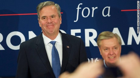Jeb Bush takes the stage with supporter Lindsey Graham before announcing the suspension of his presidential campaign at an election night party at the Hilton Columbia Center in Columbia, SC on February 20, 2016.