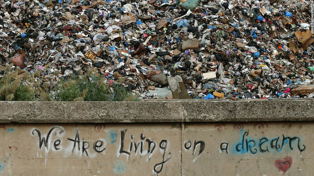 "Graffiti on a concrete wall in front of a pile of garbage in Beirut on October 17 reads, ""We are living on a dream."""