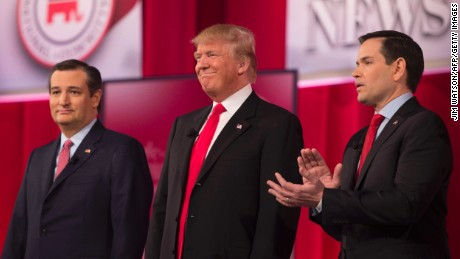 Republican presidential candidates Ted Cruz (L)and Marco Rubio (R) applaud as fellow candidate Donald Trump (C) is introduced during the CBS News Republican Presidential Debate in Greenville, South Carolina, February 13, 2016.
