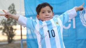Murtaza Ahmadi is pictured wearing the autographed Lionel Messi Argentina shirt given to him by the soccer superstar and UNICEF.